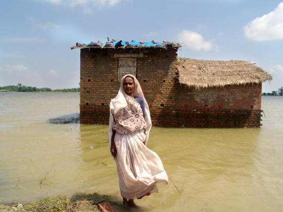 Jinsi Devi in front of her mud house that is surrounded by water with the tarpaulin on the roof which she received from CARE as part of a relief kit.